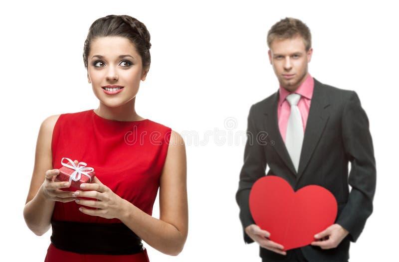 Jeune femme gaie et homme bel tenant le coeur rouge sur le blanc image stock