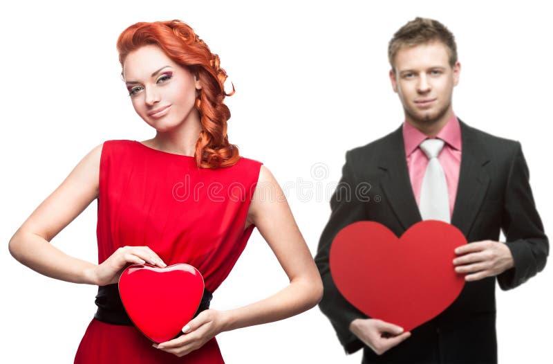 Jeune femme gaie et homme bel tenant le coeur rouge sur le blanc photographie stock libre de droits