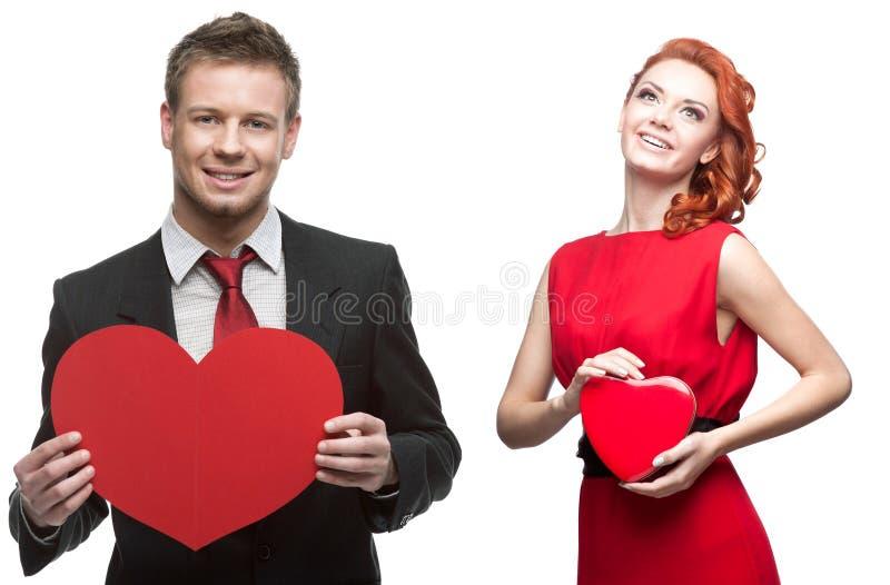 Jeune femme gaie et homme bel tenant le coeur rouge sur le blanc photos libres de droits
