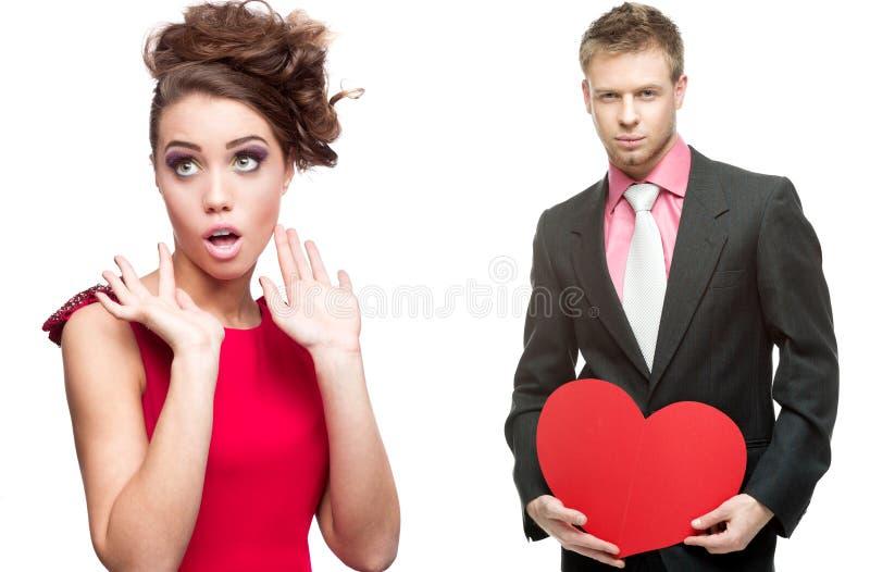 Jeune femme gaie et homme bel tenant le coeur rouge sur le blanc images stock