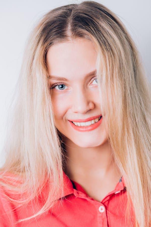 Jeune femme gaie heureuse avec la peau propre, longs cheveux blonds de maquillage naturel portant la robe rouge Il sourit et rega photo libre de droits
