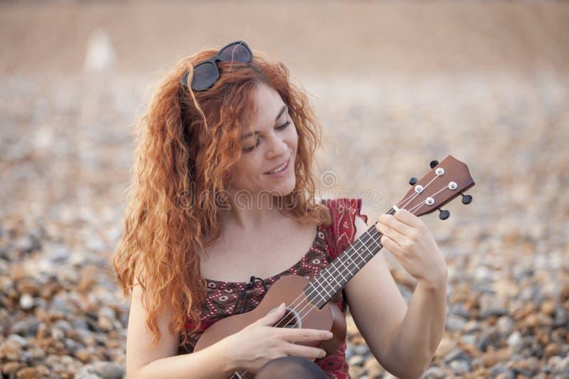 Jeune femme gaie jouant l'ukelele i photo stock