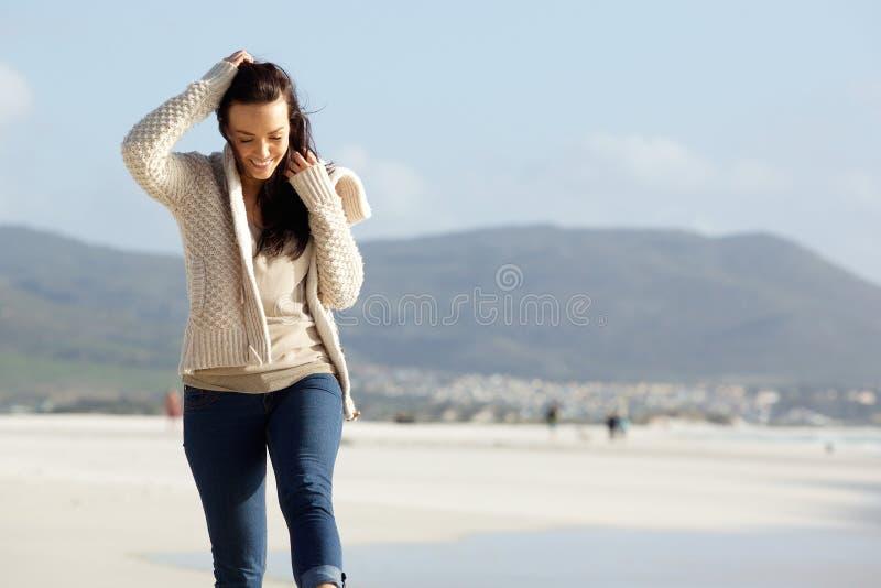 Jeune femme gaie marchant le long d'une plage images libres de droits