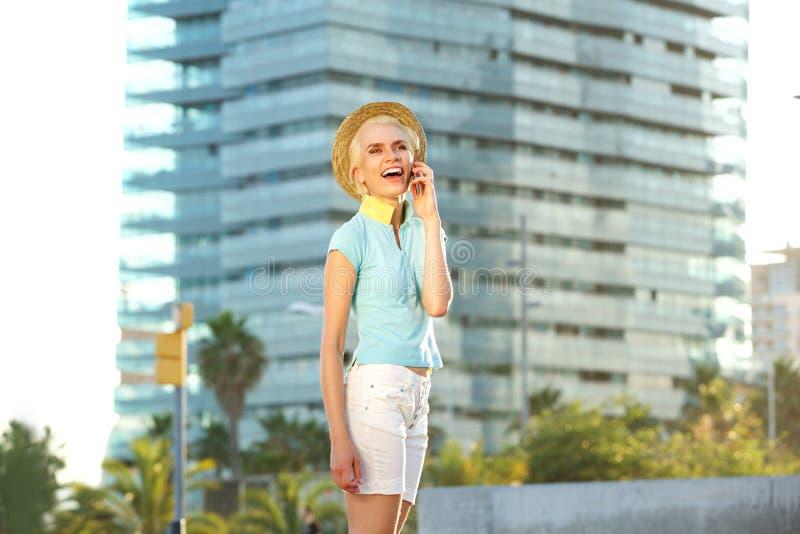 Jeune femme gaie parlant au téléphone portable dans la ville images libres de droits
