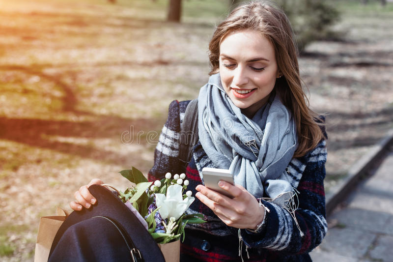 Jeune femme gaie posant tout en se photographiant sur l'appareil-photo futé de téléphone pour une causerie avec des amis, attraya images stock