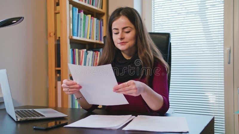 Jeune femme gaie regardant sur des documents photos libres de droits