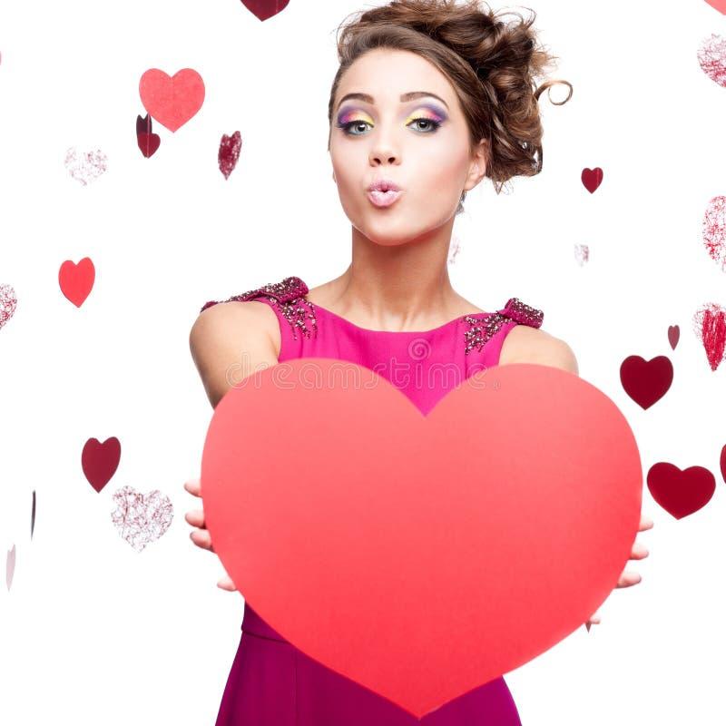 Jeune femme gaie retenant le coeur de papier rouge image stock