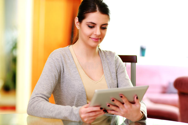 Jeune femme gaie s'asseyant à la table avec la tablette photographie stock libre de droits