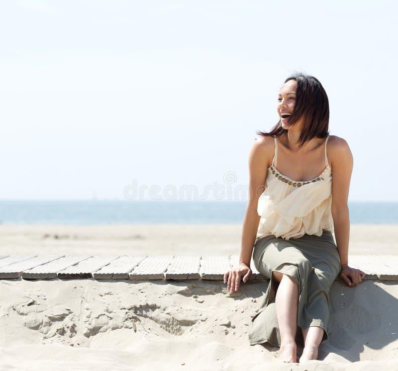 Jeune femme gaie s'asseyant par la plage photographie stock