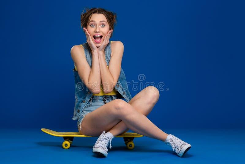 Jeune femme gaie s'asseyant sur la planche à roulettes photos libres de droits