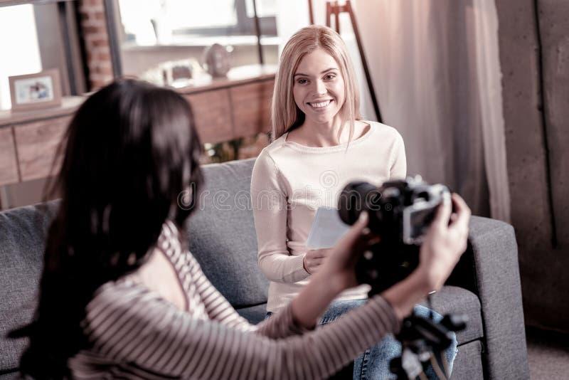 Jeune femme gaie s'asseyant sur le divan photographie stock