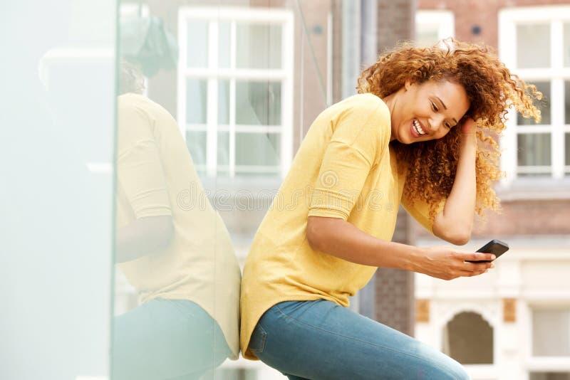 Jeune femme gaie se tenant dehors et regardant le téléphone portable image libre de droits