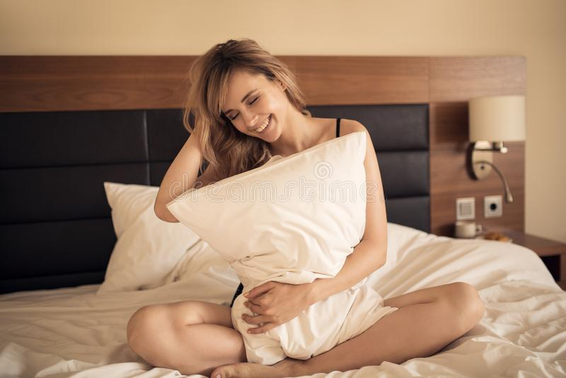 Jeune femme gaie souriant dans la chambre à coucher photo libre de droits