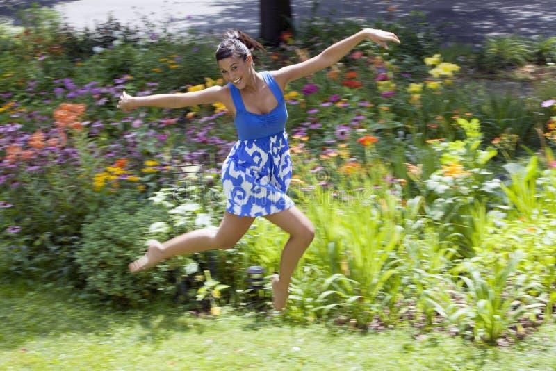 Jeune femme gambadant sur l'herbe images stock