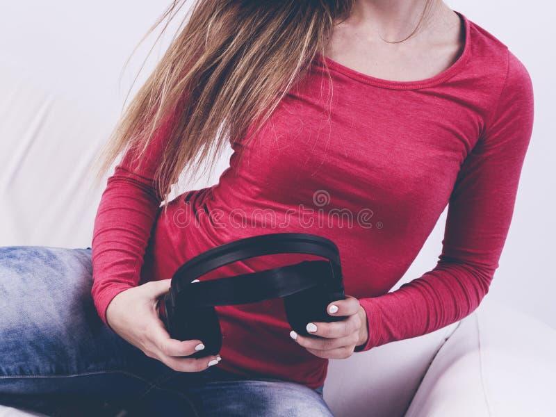 Jeune femme gardant des écouteurs image libre de droits