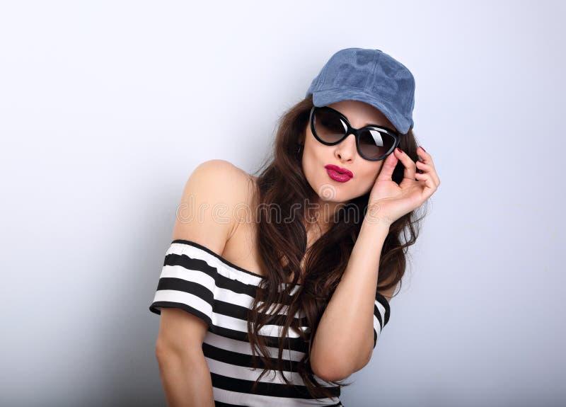 Jeune femme grimaçante de plaisir heureux dans les lunettes de soleil et les bas bleus photo stock