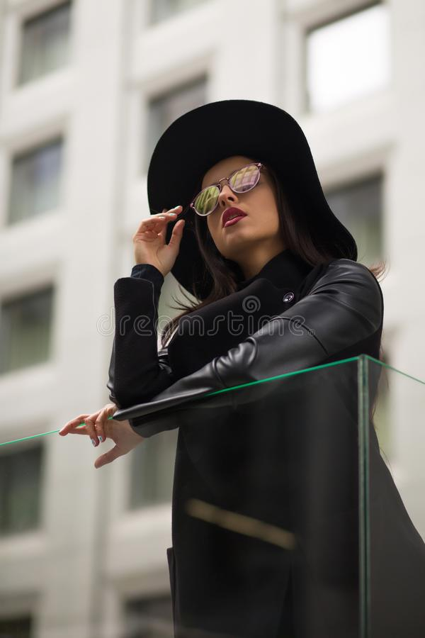 Jeune femme habillée élégante dans le chapeau noir et le miroir au loin débordés photographie stock