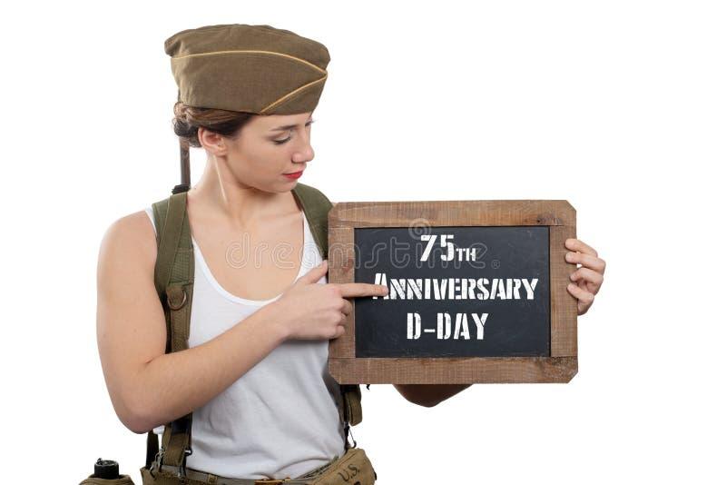 Jeune femme habill?e dans le tableau de repr?sentation uniforme militaire de l'Am?ricain ww2 avec l'anniversaire de jour J photo libre de droits