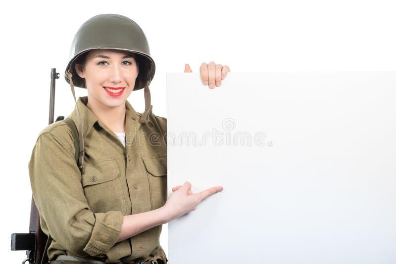 Jeune femme habillée dans les militaires ww2 nous uniforme avec le showi de casque photos stock
