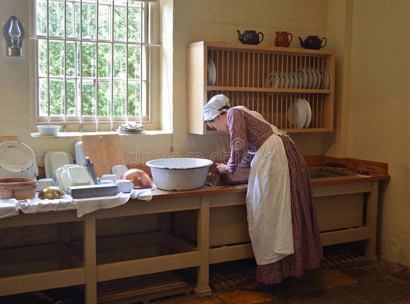 Jeune femme habillée en tant que plats de lavage de domestique de cuisine de Victoria dans l'évier photo stock