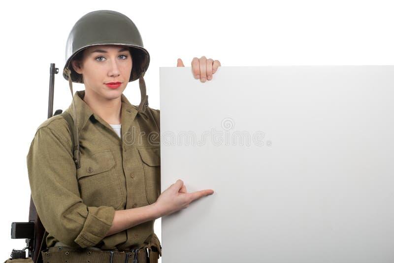 Jeune femme habill?e dans l'uniforme militaire de l'Am?ricain ww2 montrant l'enseigne vide vide image libre de droits
