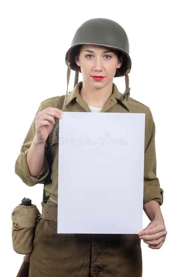 Jeune femme habill?e dans l'uniforme militaire de l'Am?ricain ww2 montrant l'enseigne vide vide image stock