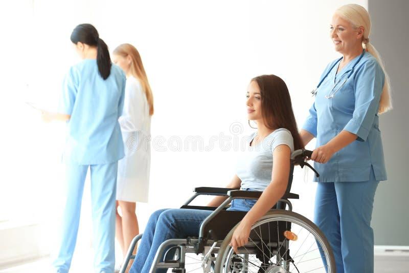 Jeune femme handicapée avec le docteur féminin mûr dans la clinique photo libre de droits