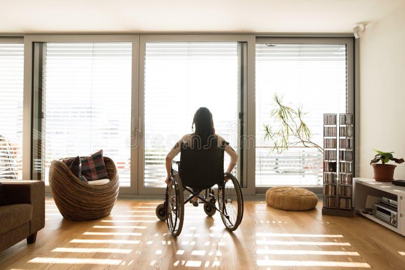 Jeune femme handicapée dans le fauteuil roulant à la maison, vue arrière photo libre de droits