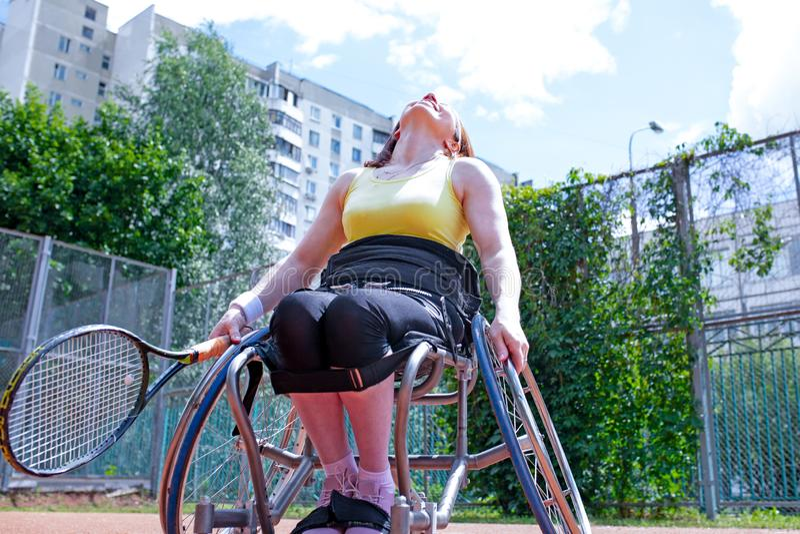 Jeune femme handicapée sur le fauteuil roulant jouant le tennis sur le court de tennis images libres de droits