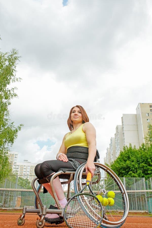 Jeune femme handicapée sur le fauteuil roulant jouant le tennis sur le court de tennis photographie stock libre de droits
