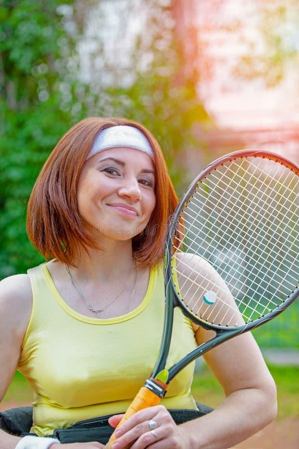 Jeune femme handicapée sur le fauteuil roulant jouant le tennis sur le court de tennis image stock
