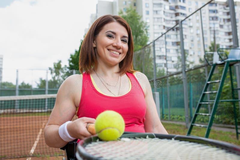 Jeune femme handicapée sur le fauteuil roulant jouant le tennis sur le court de tennis photo libre de droits