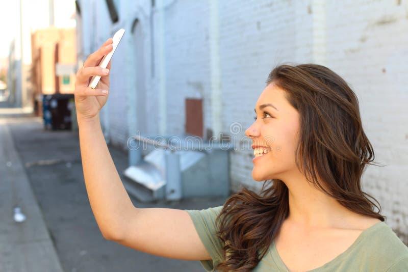 Jeune femme heureuse à l'aide d'un téléphone intelligent dans la rue avec un fond unfocused prenant un selfie ou employant Skype  images stock