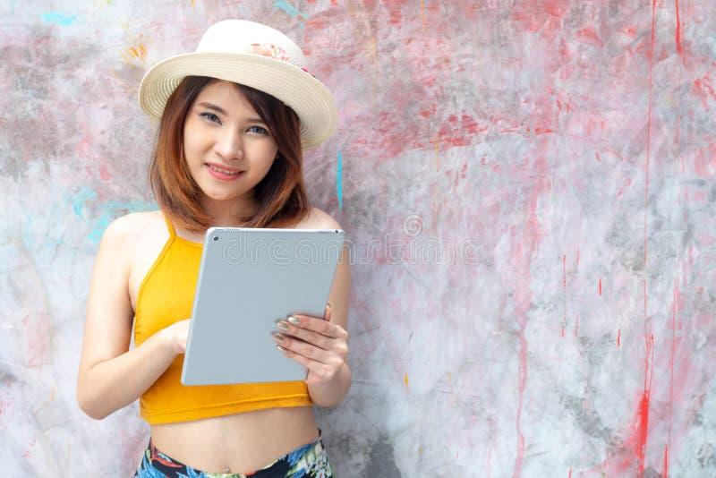Jeune femme heureuse à l'aide de la tablette au-dessus du fond de mur regardant la caméra avec l'espace de copie Joli charme de p images stock
