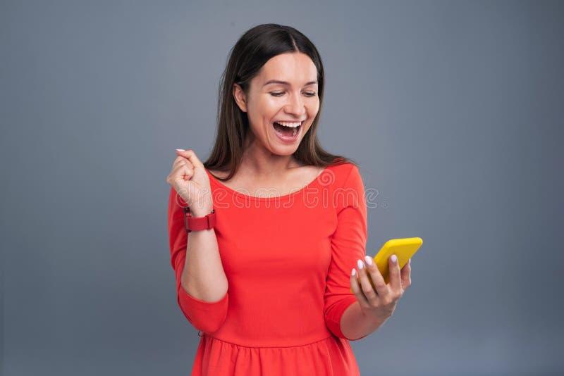 Jeune femme heureuse étant heureuse au sujet du message photographie stock