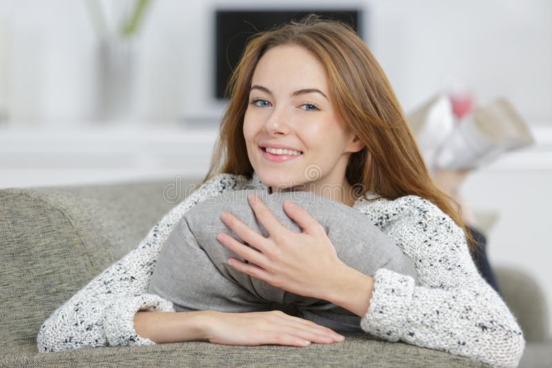Jeune femme heureuse étreignant l'oreiller gris image stock