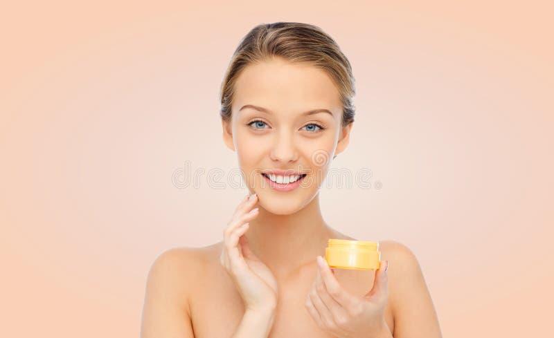 Jeune femme heureuse appliquant la crème à son visage images stock