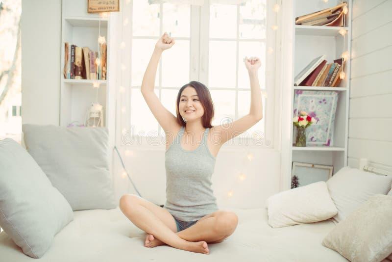 Jeune femme heureuse appr?ciant le matin ensoleill? sur le lit photographie stock