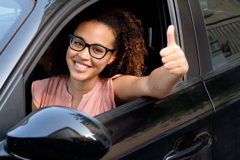 Jeune femme heureuse assise dans sa nouvelle voiture photographie stock libre de droits