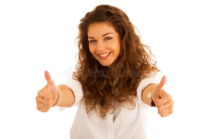 Jeune femme heureuse attirante faisant des gestes le succès montrant le pouce  photo stock