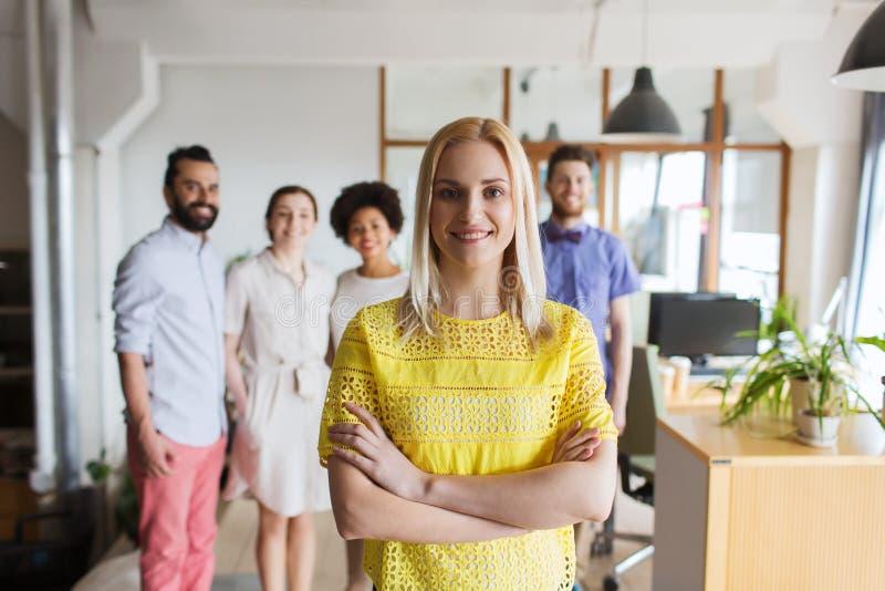 Jeune femme heureuse au-dessus d'équipe créative dans le bureau photos libres de droits