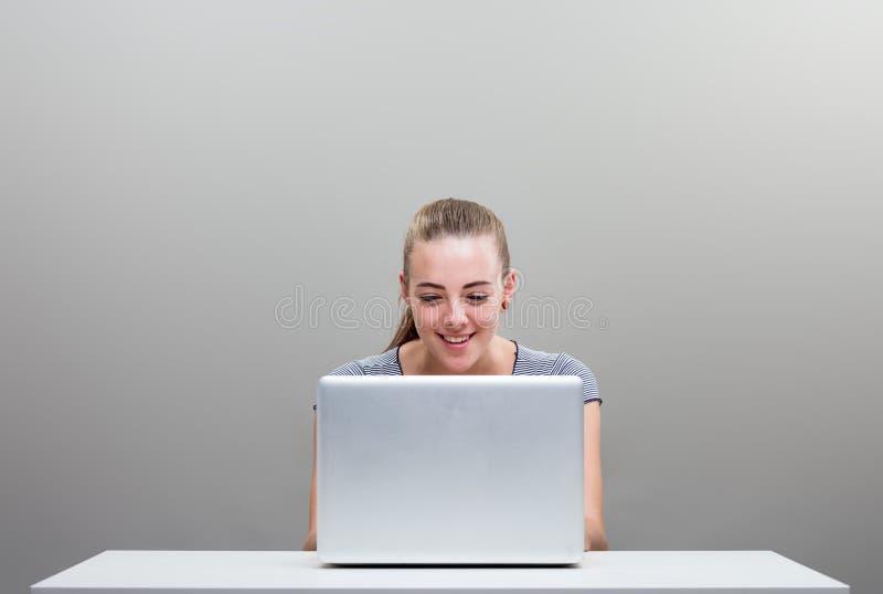Jeune femme heureuse avec l'ordinateur portable et le copyspace photo libre de droits