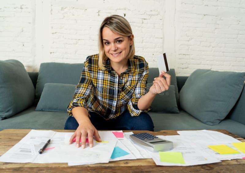 Jeune femme heureuse avec la carte de crédit entourée par des papiers calculant et des factures de paiement photographie stock