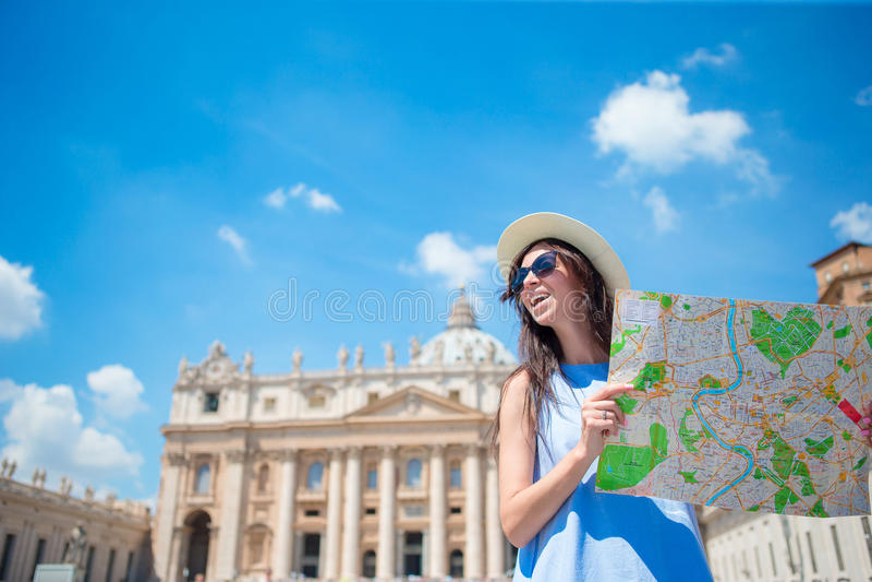 Jeune femme heureuse avec la carte de ville à Ville du Vatican et église de la basilique de St Peter, Rome, Italie Femme de touri photo stock