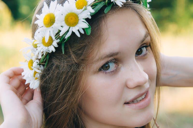 Jeune femme heureuse avec la couronne de marguerite sur la tête, extérieur de portrait de plan rapproché photos libres de droits