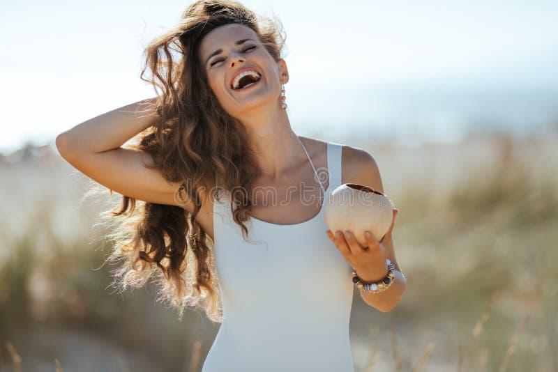 Jeune femme heureuse avec la noix de coco ajustant des cheveux sur le rivage d'océan photographie stock