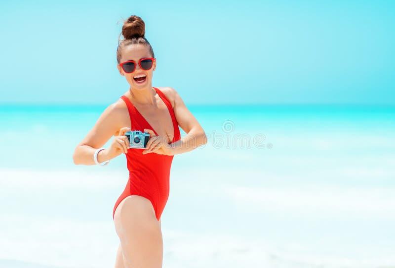 Jeune femme heureuse avec la r?tro cam?ra de photo de film sur la plage photos stock