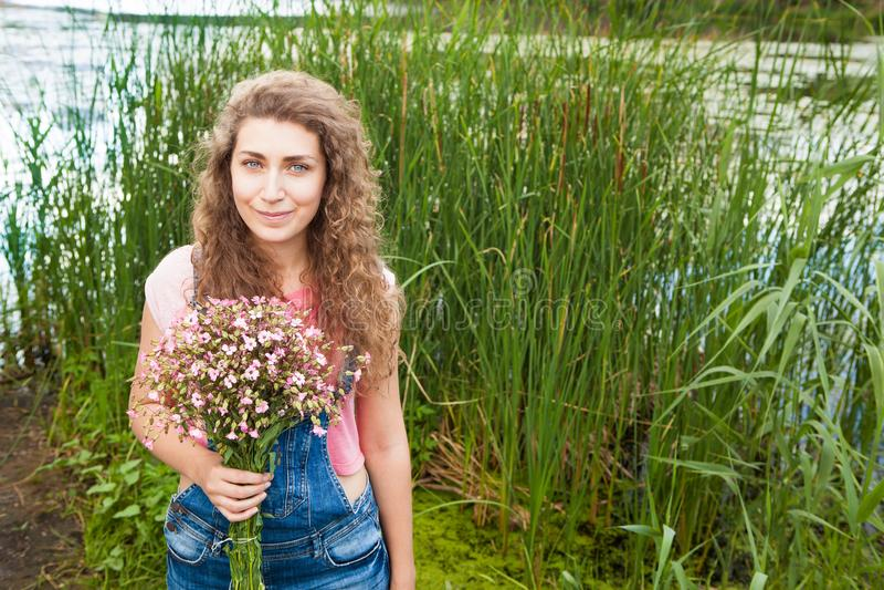 Jeune femme heureuse avec le bouquet des fleurs roses comme cadeau en été photographie stock
