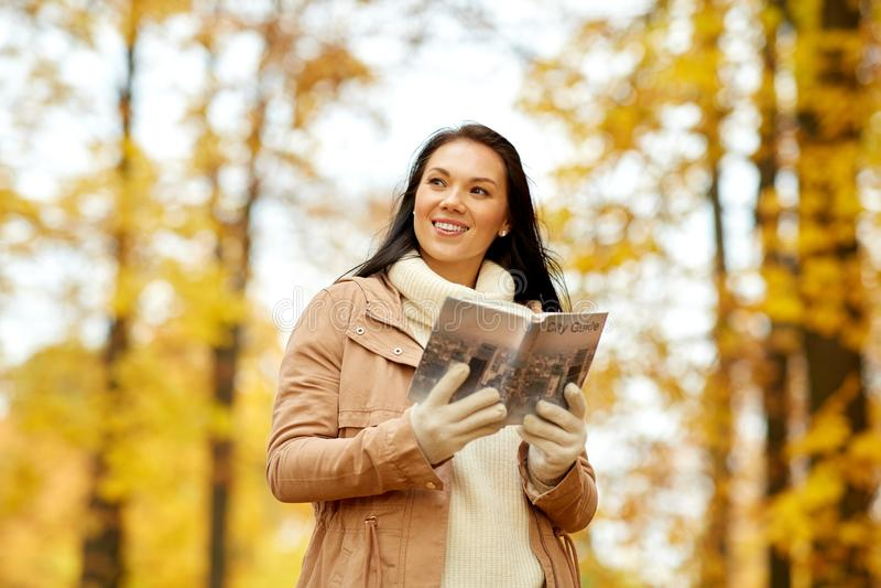 Jeune femme heureuse avec le guide de ville en parc d'automne image libre de droits
