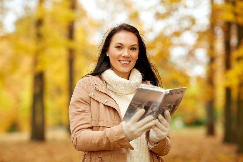 Jeune femme heureuse avec le guide de ville en parc d'automne photographie stock